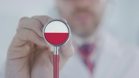 diagnóstico : Doctor uses stethoscope with the Polish flag. Healthcare in Poland