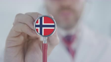diagnóstico : Medical doctor listening with the stethoscope with flag of Norway. Norwegian healthcare