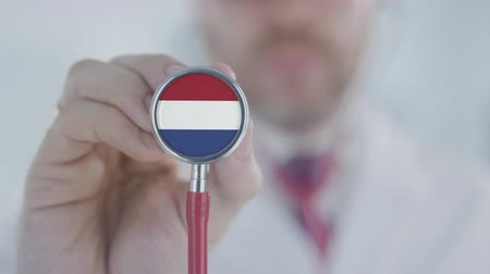 diagnóstico : Medical doctor holds stethoscope bell with the Dutch flag. Healthcare in Netherlands Stock Footage