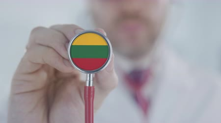 terapeuta : Doctor holds stethoscope bell with the Lithuanian flag. Healthcare in Lithuania Stock Footage