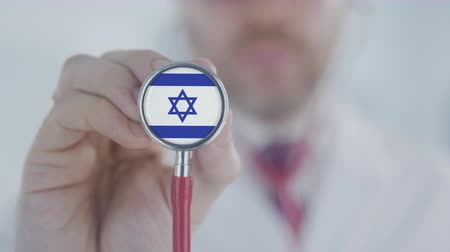 diagnóstico : Doctor uses stethoscope with the Israeli flag. Healthcare in Israel Stock Footage