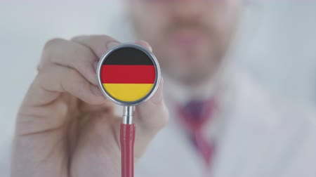 diagnóstico : Physician holds stethoscope bell with the German flag. Healthcare in Germany