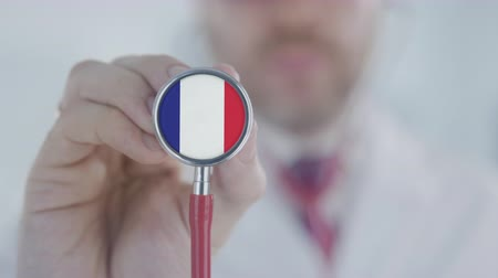 md : Doctor listening with the stethoscope with flag of France. French healthcare