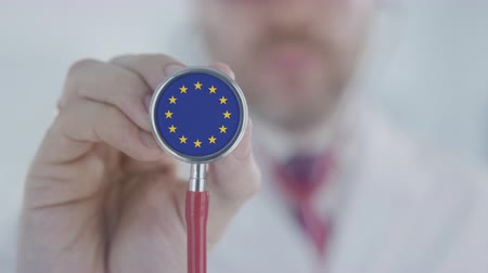 diagnóstico : Doctor listening with the stethoscope with flag of the EU. European healthcare Stock Footage