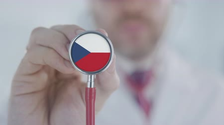 diagnóstico : Doctor holds stethoscope bell with the Czech flag. Healthcare in the Czech Republic