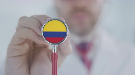 md : Physician uses stethoscope with the Colombian flag. Healthcare in Colombia