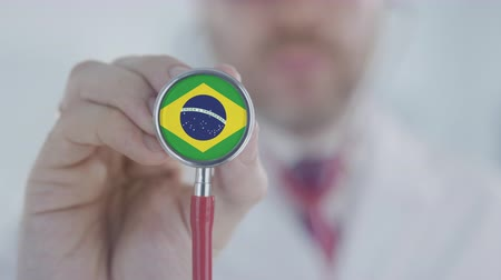 diagnóstico : Doctor uses stethoscope with the Brazilian flag. Healthcare in Brazil