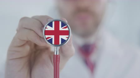 bretanha : Doctor listening with the stethoscope with flag of the UK. British healthcare Vídeos