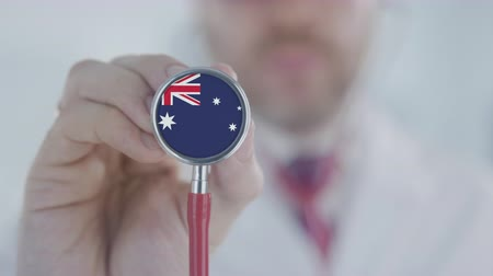 diagnóstico : Doctor uses stethoscope with the Australian flag details. Healthcare in Australia