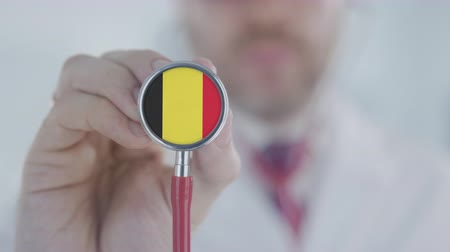 diagnóstico : Doctor listening with the stethoscope with flag of Belgium. Belgian healthcare