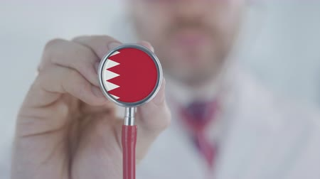 diagnóstico : Doctor uses stethoscope with the Bahraini flag. Healthcare in Bahrain Stock Footage
