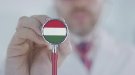 diagnóstico : Physician uses stethoscope with the Hungarian flag. Healthcare in Hungary