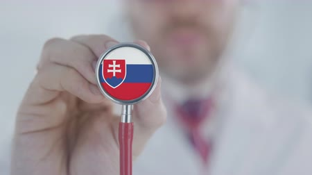 diagnóstico : Medical doctor holds stethoscope bell with the Slovak flag. Healthcare in Slovakia Stock Footage