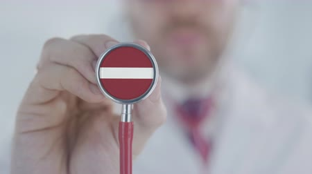 diagnóstico : Doctor listening with the stethoscope with flag of Latvia. Latvian healthcare Stock Footage