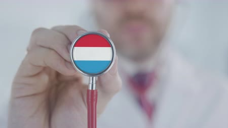 diagnóstico : Doctor listening with the stethoscope with flag of Luxembourg. Luxembourgian healthcare