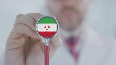 diagnóstico : Doctor uses stethoscope with the Iranian flag. Healthcare in Iran