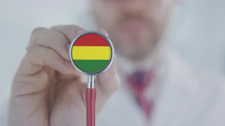 diagnóstico : Doctor holds stethoscope bell with the Bolivian flag. Healthcare in Bolivia Stock Footage