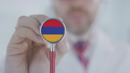 diagnóstico : Physician listening with the stethoscope with flag of Armenia. Armenian healthcare