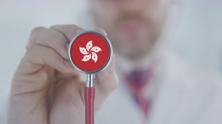 diagnóstico : Physician uses stethoscope with the flag. Healthcare in Hong Kong Stock Footage