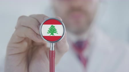 доктор : Doctor holds stethoscope bell with the Lebanonese flag. Healthcare in Lebanon Стоковые видеозаписи