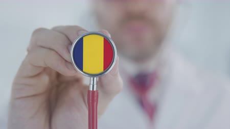 terapeuta : Doctor uses stethoscope with the Romanian flag. Healthcare in Romania Stock Footage