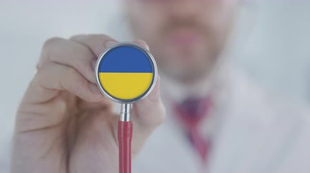diagnóstico : Doctor listening with the stethoscope with flag of Ukraine. Ukrainian healthcare