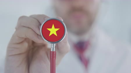 diagnóstico : Doctor holds stethoscope bell with the Vietnamese flag. Healthcare in Vietnam