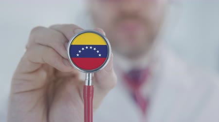 diagnóstico : Doctor holds stethoscope bell with the Venezuelan flag. Healthcare in Venezuela