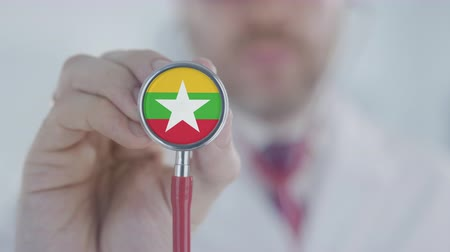diagnóstico : Medical doctor holds stethoscope bell with the Myanma flag. Healthcare in Myanmar