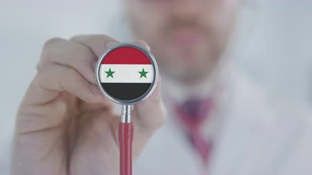 держит : Doctor uses stethoscope with the Syrian flag. Healthcare in Syria