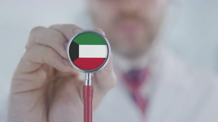 diagnóstico : Physician holds stethoscope bell with the Kuwaiti flag. Healthcare in Kuwait Stock Footage