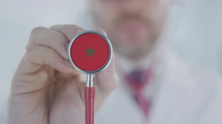 diagnóstico : Medical doctor holds stethoscope bell with the Moroccan flag. Healthcare in Morocco