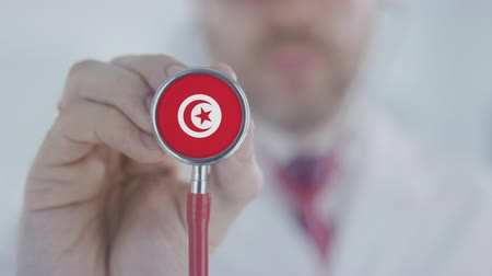 diagnóstico : Doctor holds stethoscope bell with the Tunisian flag. Healthcare in Tunisia Stock Footage