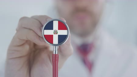 diagnóstico : Doctor uses stethoscope with the Dominican flag. Healthcare in the Dominican Republic