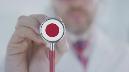 diagnóstico : Doctor listening with the stethoscope with flag of Japan. Japanese healthcare Stock Footage