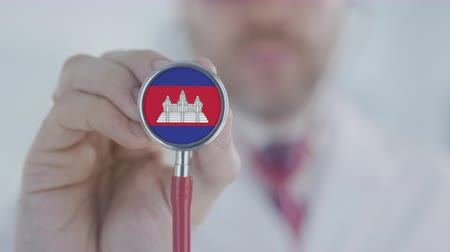 cambojano : Physician holds stethoscope bell with the Cambodian flag. Healthcare in Cambodia