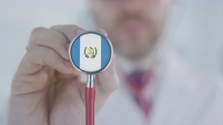 diagnóstico : Physician listening with the stethoscope with flag of Guatemala. Guatemalan healthcare