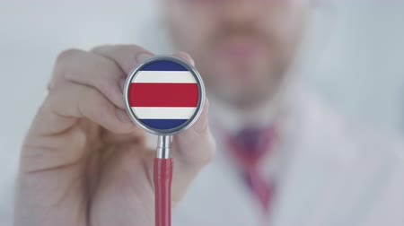 diagnóstico : Physician listening with the stethoscope with flag of Costa Rica. Costa Rican healthcare