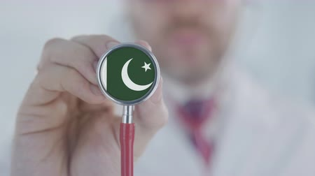 diagnóstico : Medical doctor listening with the stethoscope with flag of Pakistan. Pakistani healthcare Stock Footage