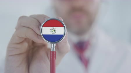 diagnóstico : Medical doctor listening with the stethoscope with flag of Paraguay. Paraguayan healthcare