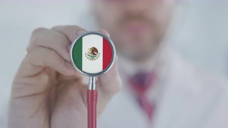 diagnóstico : Doctor holds stethoscope bell with the Mexican flag. Healthcare in Mexico