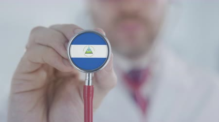 diagnóstico : Medical doctor listening with the stethoscope with flag of Nicaragua. Nicaraguan healthcare Stock Footage