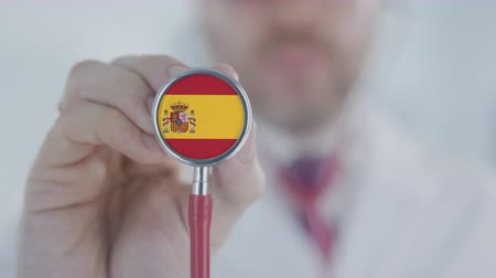 diagnóstico : Medical doctor listening with the stethoscope with flag of Spain. Spanish healthcare