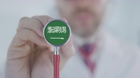 diagnóstico : Doctor uses stethoscope with the Saudi Arabian flag. Healthcare in Saudi Arabia Stock Footage