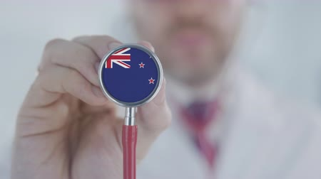 diagnóstico : Medical doctor holds stethoscope bell with the national flag. Healthcare in New Zealand
