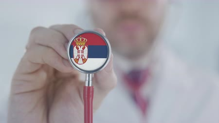 diagnóstico : Doctor holds stethoscope bell with the Serbian flag. Healthcare in Serbia