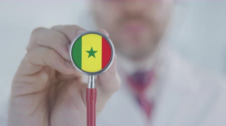 diagnóstico : Doctor uses stethoscope with the Senegalese flag. Healthcare in Senegal Stock Footage