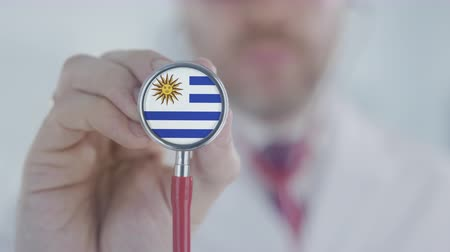 diagnóstico : Doctor holds stethoscope bell with the Uruguayan flag. Healthcare in Uruguay