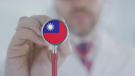 diagnóstico : Doctor listening with the stethoscope with flag of Taiwan. Taiwanese healthcare Stock Footage