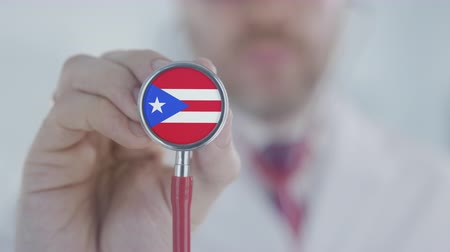 diagnóstico : Doctor holds stethoscope bell with the Puerto Rican flag. Healthcare in Puerto Rico